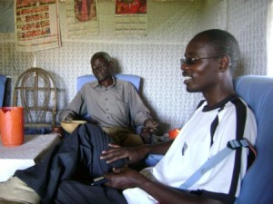 OHR Executive Director, Richard Magerenge (right), discusses the radio and Internet tower with Mzee Okello (left) during land negotiations at his home atop Soklo mountain on Mfangano Island.